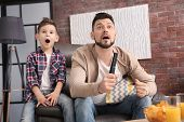 Father and son watching sports on TV at home poster
