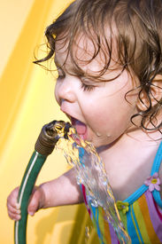 picture of drinking water  - a toddler drinking water from a garden hose - JPG