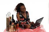 picture of internet-cafe  - Pretty young African American business woman working on a laptop computer while enjoying a beverage at an Internet Cafe - JPG