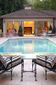 picture of open door  - Two lounge chairs over look an inviting pool and a pool house - JPG