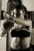 Dedicated young female fighter throwing a flurry of punches on the heavy bag Motion blur on her hands poster