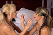 Two sexy young women applying each others makeup while at a slumber party pic.