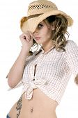 stock photo of bare midriff  - Sexy young cowgirl in a checkered blouse and straw cowboy hat - JPG