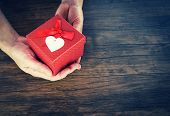 Give Love Man Holding Small Red Present Box In Hands With Heart For Love Valentines Day Concept / Gi poster