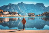 Young Woman Standing On The Coast Of Misurina Lake At Sunrise In Autumn. Dolomites, Italy. Landscape poster