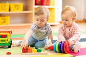 Preschool Boy And Girl Playing On Floor With Educational Toys. Children Toddlers At Home Or Daycare. poster