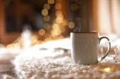 Cup Of Hot Beverage On Fuzzy Rug Against Blurred Background, Space For Text. Winter Evening poster