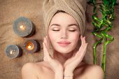Beautiful spa woman with a towel on her head lying and touching face skin. Skincare. Beauty smiling  poster