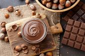 Chocolate Spread Or Nougat Cream With Hazelnuts In Glass Jar, Bowl Of Nuts And Chocolate Bars On Tab poster