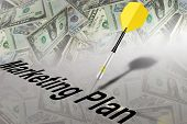 foto of marketing plan  - Yellow and black dart stuck on table with money and text - JPG