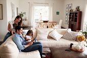 Young Hispanic family sitting on sofa reading a book together in their living room poster
