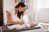 Happy mother changing the diaper of her newborn son at home on a baby changing table, waist up poster