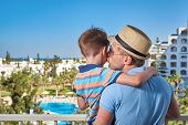 Son And Dad Relaxing On Hotel Balcony On Summer Holidays. Father Is Holding Son On Hands. Dad Is Kis poster