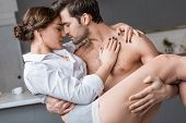 Passionate Shirtless Man Holding In Arms Attractive Girlfriend poster