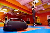 Portable Acoustics In The Aerobics Room Against The Background Of A Blurred Girl On Cardio Training. poster