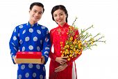 Happy Young Asian Couple Holding Traditional Tet Symbols: Blooming Apricot Branches And Red And Gold poster