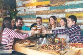 Happy Young Hipster Friends Celebrating By Toasting With Beer Eating Pizza And Burgers At Bar Restau poster