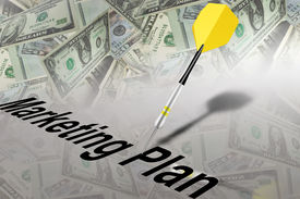 picture of marketing plan  - Yellow and black dart stuck on table with money and text - JPG