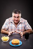picture of greedy  - Portrait of a greedy man looking at burger on gray background - JPG