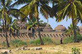 stock photo of vijayanagara  - Palm trees and the back side of Elephant Stable in Hampi Karnataka India - JPG