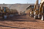 picture of open-pit mine  - Rows of heavy earth moving equipment in open pit mine - JPG