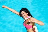 stock photo of superwoman  - Playful woman playing around in swimming pool on summer vacation - JPG