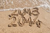 stock photo of new year 2014  - Waves delete numbers of old year 2013  - JPG