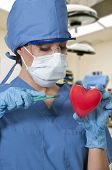 stock photo of open heart surgery  - Beautiful young woman cardiology surgeon performing surgery - JPG