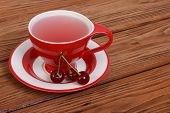 Fruit tea with cherry berries on brown wooden
