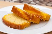 stock photo of sponge-cake  - Sliced lemon drizzle cake presented on a white plate - JPG