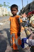 stock photo of beggars  - A poor Indian beggar girl anxiously standing by the side of a street - JPG