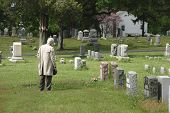picture of life after death  - An elderly man pays his respects at a cemetery - JPG