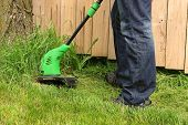 foto of electric trimmer  - Man cutting the grass with electric trimmer - JPG