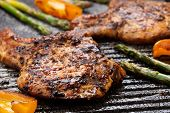 stock photo of pork  - Juicy pork chops are grilled on griddle with asparagus and bell pepper - JPG