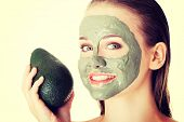stock photo of avocado  - Beautiful spa woman in facial mask and avocado - JPG