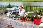 stock photo of planters  - Senior lady working in her summer kitchen on an outdoor brick patio caring for and potting up her houseplants in a variety of flowerpots and planters - JPG