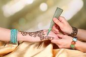 stock photo of mehndi  - Process of applying Mehndi on female hand - JPG