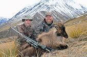 stock photo of hunter  - Hunters pose with their Himalayan tahr in the Southern Alps of New Zealand  - JPG