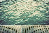 stock photo of jetties  - Grunge wood boards of a pier over ocean with rippling waves - JPG