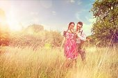 picture of lederhosen  - Loving couple in traditional Bavarian Dirndl and Lederhosen eat a brezel outside - JPG