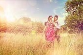picture of lederhosen  - Loving couple in traditional Bavarian Dirndl and Lederhosen eat a brezel outside - JPG