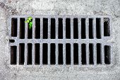 stock photo of metal grate  - Metal drain grate in the sandy surface - JPG