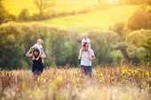 foto of mother baby nature  - Happy family enjoying life together at meadow outdoor.