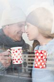 image of glass-wool  - Happy couple in warm clothing holding mugs seen through glass window - JPG