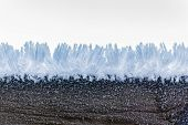 picture of ice crystal  - macro shot of a wooden fence covered with ice crystals due to the hoarfrost in winter - JPG
