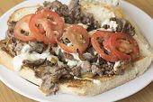 foto of cheesesteak  - Messy cheesesteak sandwich with sliced tomatoes and a rich creamy horseradish sauce with side of macaroni salad - JPG