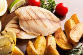 stock photo of halibut  - Fried halibut with vegetables and fruits on the table - JPG