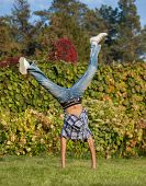 picture of parkour  - student in casual wear show handspring ouutdoor in park - JPG