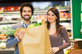 image of supermarket  - Couple holding a bag full of vegetables at supermarket - JPG