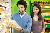 foto of supermarket  - Couple shopping in a supermarket - JPG